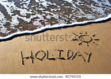 The word holiday written in sand - stock photo