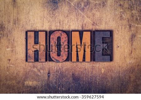 """The word """"Home"""" written in dirty vintage letterpress type on a aged wooden background. - stock photo"""
