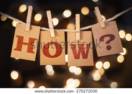 The word HOW? printed on clothespin clipped cards in front of defocused glowing lights. - stock photo
