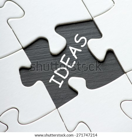 The word IDEAS revealed on a blackboard by a missing jigsaw puzzle piece - stock photo