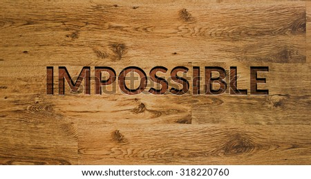 The word IMPOSSIBLE Engraved in Wooden Background. - stock photo