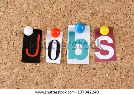 The word Jobs in cut out magazine letters pinned to a cork notice board - stock photo
