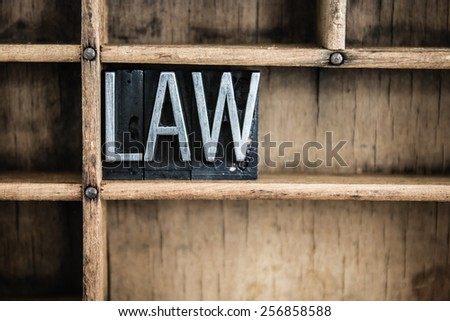 "The word ""LAW"" written in vintage metal letterpress type in a wooden drawer with dividers. - stock photo"