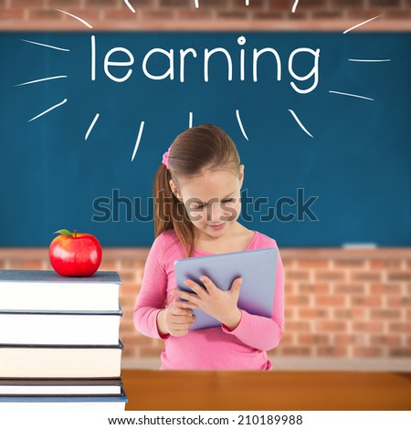 The word learning and cute girl using tablet against red apple on pile of books in classroom - stock photo
