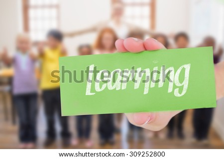 The word learning and hand showing card against teacher and pupils smiling at camera in classroom - stock photo