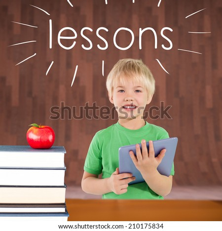 The word lessons and cute boy using tablet against red apple on pile of books