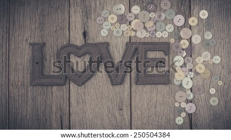 The Word Love and Close up sewing buttons on wooden background. - stock photo