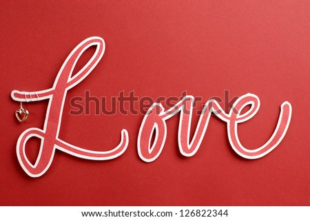 The word, Love, in letters with cute heart against a red background, for Valentine, Christmas, Easter, birthday, or Mothers Day. - stock photo