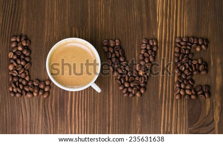"The word ""love"" made from coffee beans on a wooden background - stock photo"