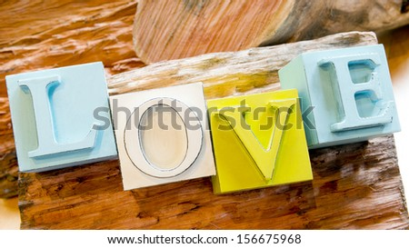The word Love spelled out in big block letters on a rustic wooden background - stock photo
