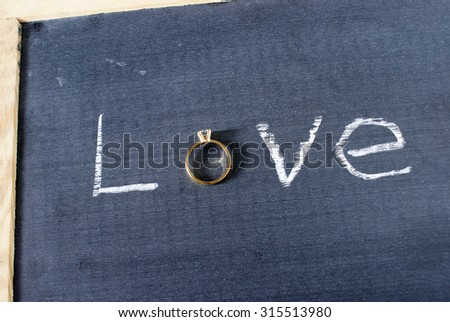 The word love spelled out on a chalkboard with a letter replaced with a diamond ring. - stock photo
