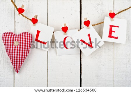 """the word """"Love"""" written on pieces of paper hanged up to a rope - stock photo"""