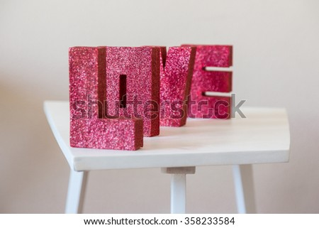 The word LOVE written with cardboard letters covered with tinsel standing on a white table - stock photo