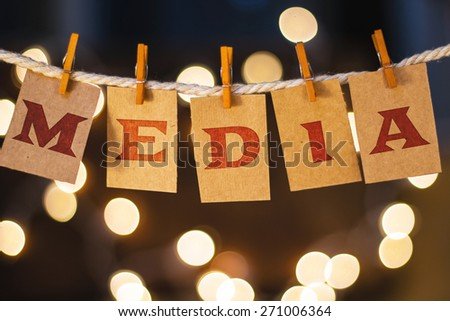 The word MEDIA printed on clothespin clipped cards in front of defocused glowing lights. - stock photo