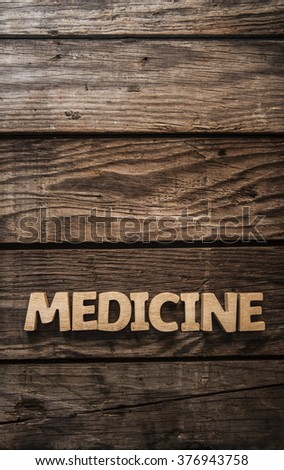"The word ""MEDICINE"" theme written in vintage, wooden letterpress type on a wood grained background."