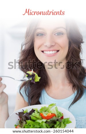 The word micronutrients against brunette having salad - stock photo