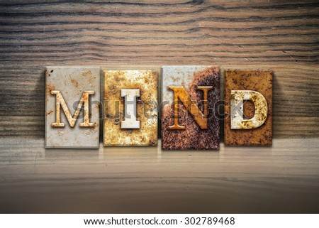 "The word ""MIND"" written in rusty metal letterpress type sitting on a wooden ledge background. - stock photo"