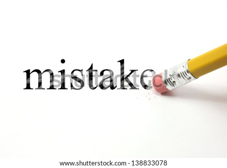 The word mistake written with a pencil on white paper.  An eraser from a pencil is starting to erase the word mistake. - stock photo
