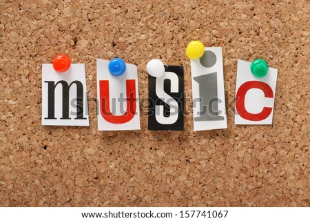 The word Music in cut out magazine letters pinned to a cork notice board.