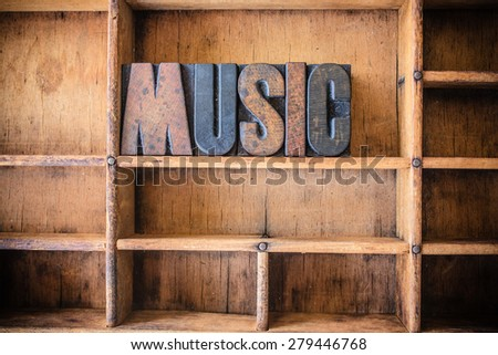 The word MUSIC written in vintage wooden letterpress type in a wooden type drawer. - stock photo