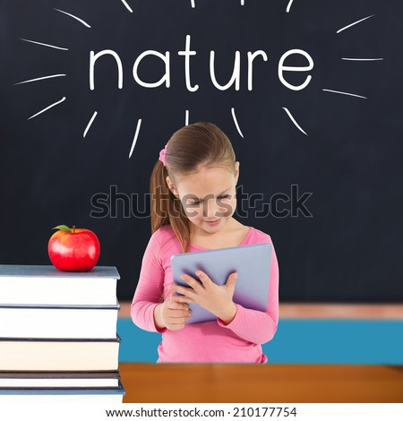 The word nature and cute girl using tablet against red apple on pile of books in classroom - stock photo