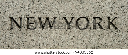 "The word ""New York"" carved into granite"