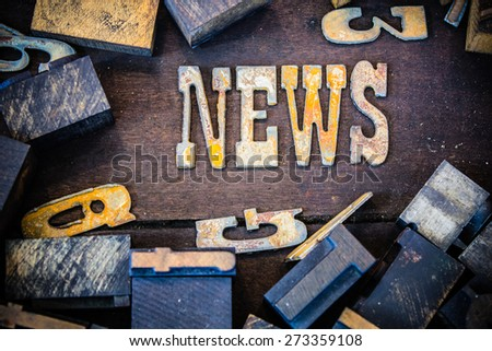 The word NEWS written in rusted metal letters surrounded by vintage wooden and metal letterpress type. - stock photo