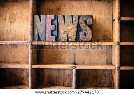 The word NEWS written in vintage wooden letterpress type in a wooden type drawer. - stock photo