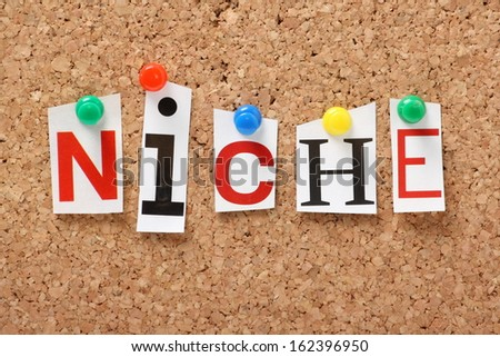 The word Niche in cut out magazine letters pinned to a cork notice board. Businesses look for niche products, brands and markets to generate sales and profit.