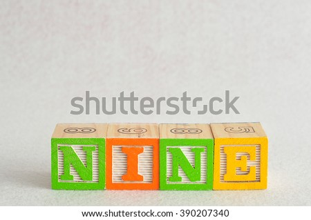 The word nine (9) spelled with colorful alphabet blocks isolated against a white background - stock photo