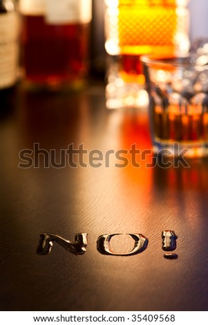 The word No! written with spoiled whiskey on a table, shallow DOF - stock photo