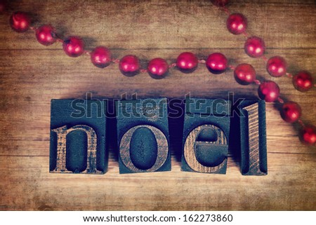 The word NOEL written with vintage wood printer blocks. Christmas message over old wood with a string of decorative red beads. - stock photo