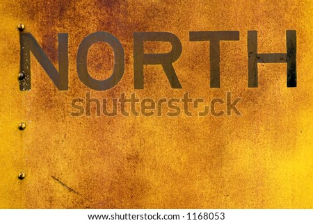 The word North is old and faded and painted on the side of a old train car. - stock photo
