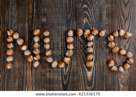 "The word ""nuts"" of hazelnut on dark wooden background"