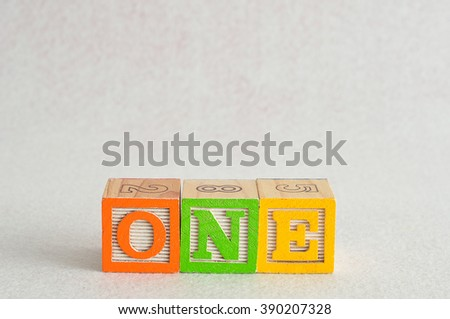 The word one (1) spelled with colorful alphabet blocks isolated against a white background - stock photo