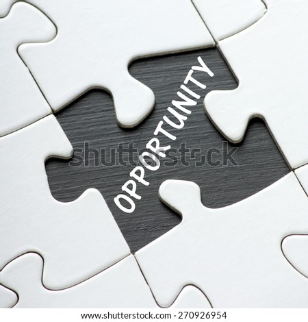 The word OPPORTUNITY revealed on a blackboard by a missing jigsaw puzzle piece - stock photo
