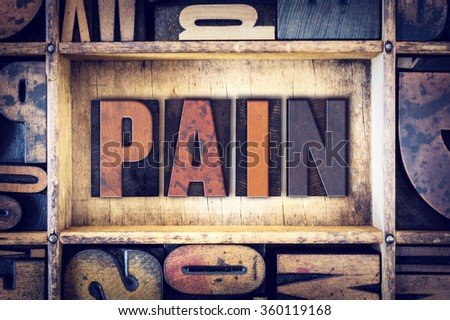 "The word ""Pain"" written in vintage wooden letterpress type."