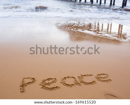 The word 'Peace' written in the sand, with the sea in the background. - stock photo