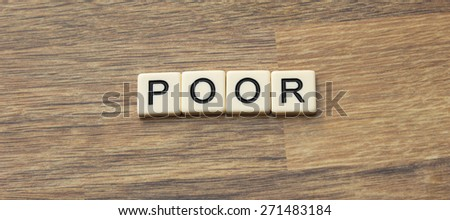 The word poor written in tiles on a wooden surface
