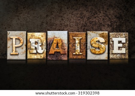"The word ""PRAISE"" written in rusty metal letterpress type on a dark textured grunge background. - stock photo"