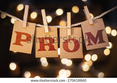The word PROM printed on clothespin clipped cards in front of defocused glowing lights. - stock photo