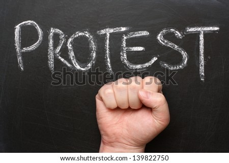 The word Protest written in chalk on a blackboard with a clenched male fist delivering a power salute