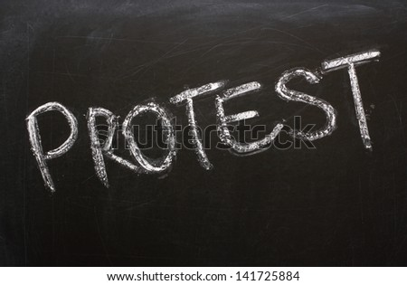 The word Protest written in chalk on a used blackboard