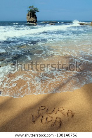 "The word ""pura vida"" written on the sand in a tropical beach with rocky islet, Caribbean, Costa Rica"