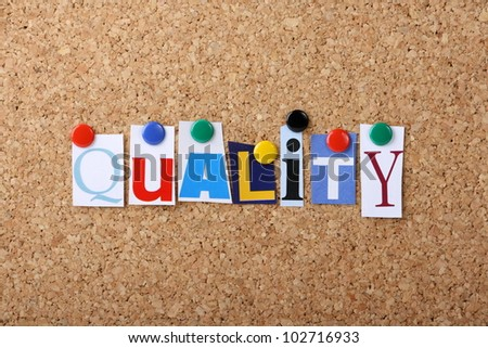The word Quality in cut out magazine letters pinned to a cork notice board