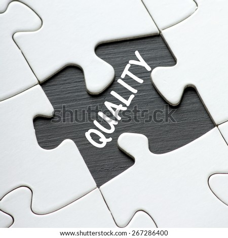 The word QUALITY revealed on a blackboard by a missing jigsaw puzzle piece - stock photo