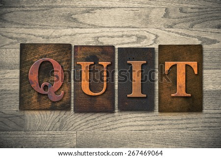 """The word """"QUIT"""" theme written in vintage, ink stained, wooden letterpress type on a wood grained background. - stock photo"""