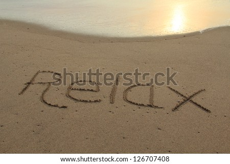 The word relax hand written in the sand at sunset. - stock photo