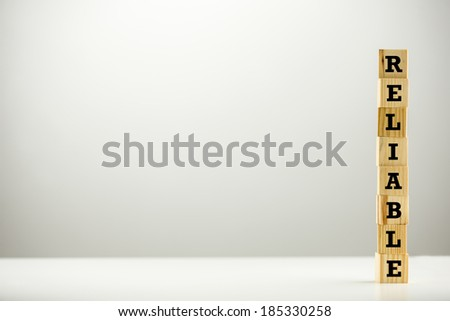 The word - Reliable - on a tower of stacked wooden cubes positioned to the right hand side against a grey studio background with plenty of copyspace. - stock photo