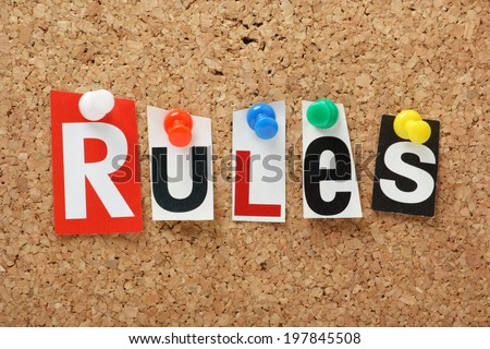 The word Rules in cut out magazine letters on a cork notice board  - stock photo